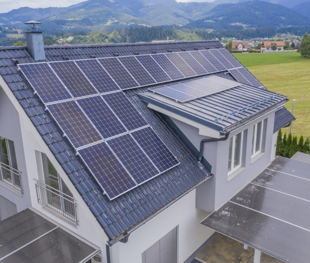 High angle shot of a private house situated in a valley with solar panels on the roof