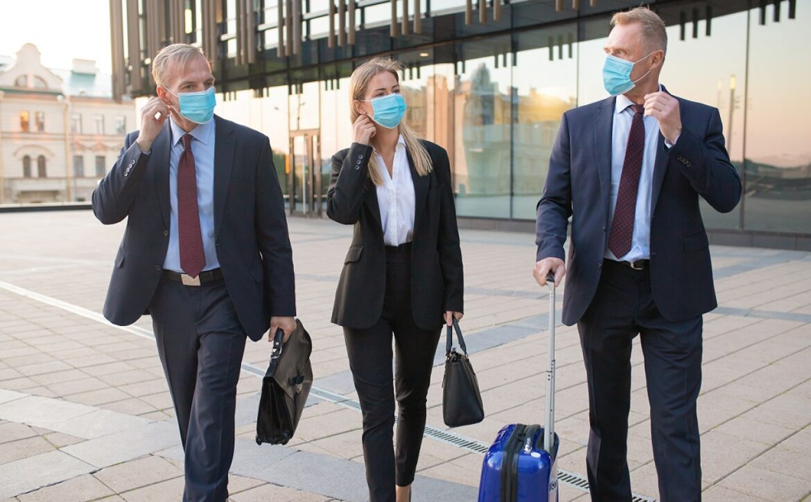Business tourists in face masks travelling with briefcases