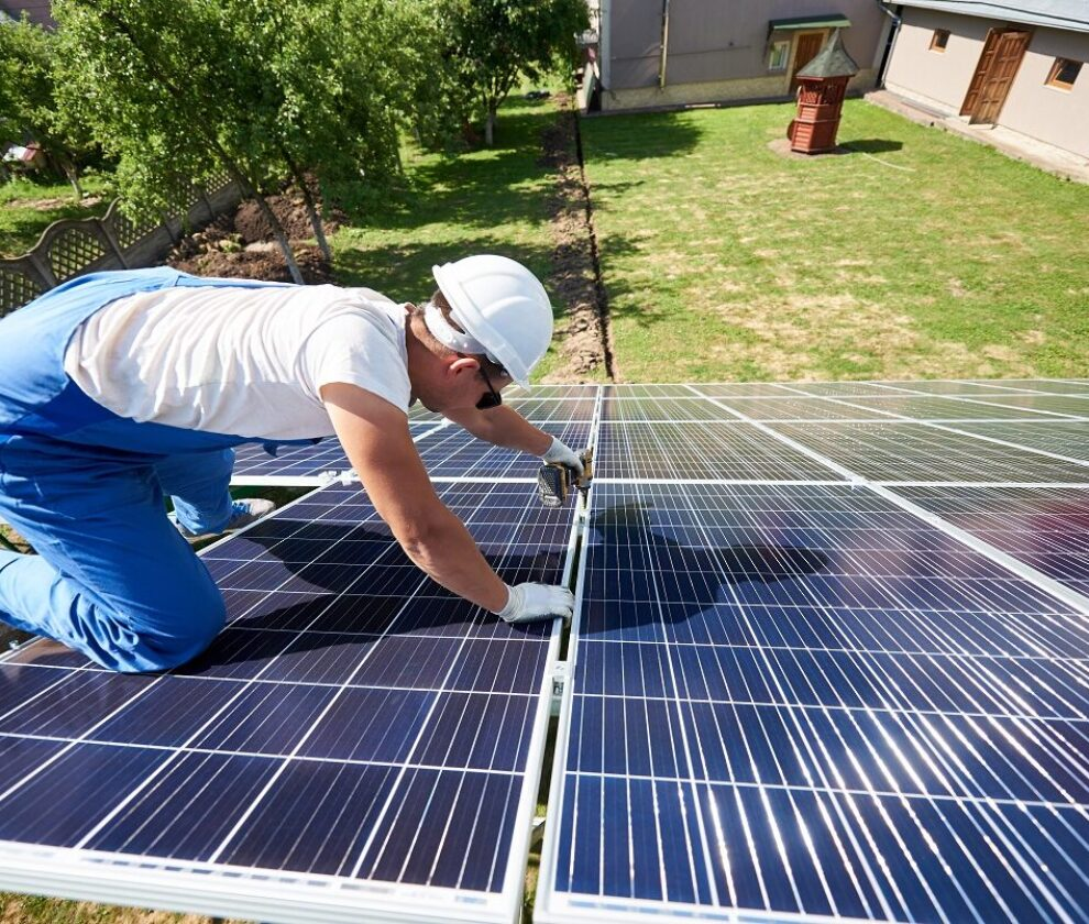 Professional worker installing solar panels on the green metal construction