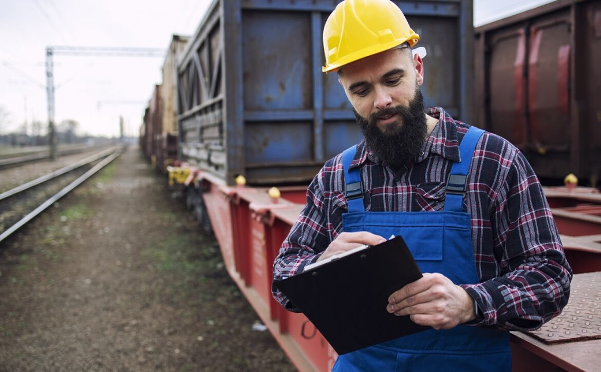 Worker dispatching cargo containers for shipping companies via freight train and organizing goods to be exported.